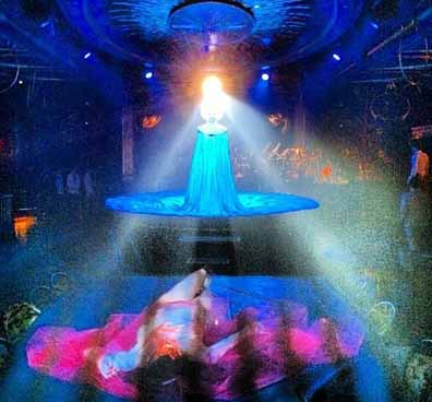 Queen of the Night Mask,  photo of Katherine Crockett standing in a blue dress with a lazer light hitting the stone at the top of the mask and reflecting throughout the theater.