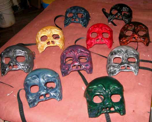 10 finished skull masks, green, gray silver, light blue, silver, yellow, blue, red , black and browish red all laying on a table in my workshop